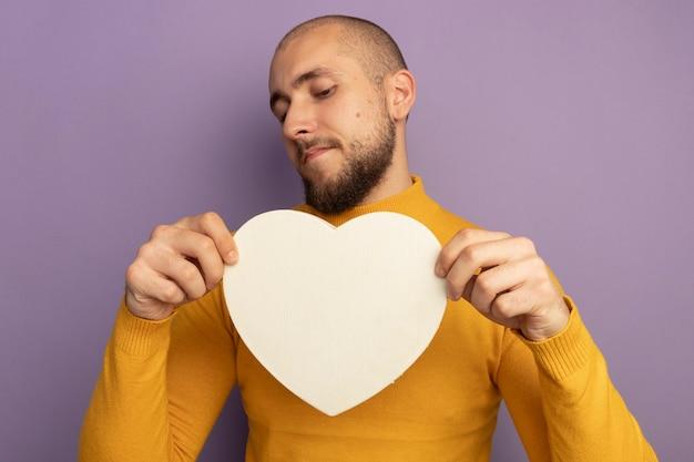 Niezadowolony młody przystojny facet trzymając i patrząc na pudełko w kształcie serca na białym tle na fioletowej ścianie