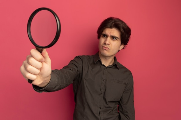 Niezadowolony młody przystojny facet ubrany w czarną koszulkę, trzymając i patrząc na lupę na białym tle na różowej ścianie