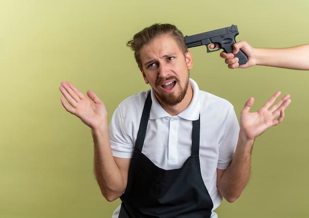 Niezadowolony młody przystojny fryzjer patrząc z boku, pokazując puste dłonie z kimś wskazującym pistolet na głowie na białym tle na oliwkowym tle