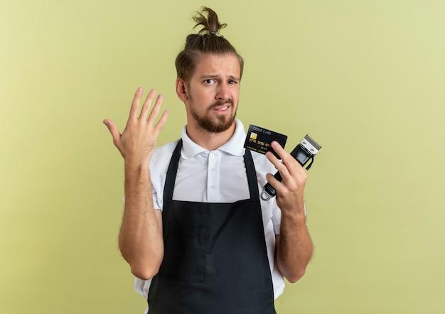 Niezadowolony młody przystojny fryzjer trzyma kartę kredytową i maszynkę do strzyżenia włosów, podnosząc rękę na białym tle na oliwkowozielonym tle z miejsca na kopię
