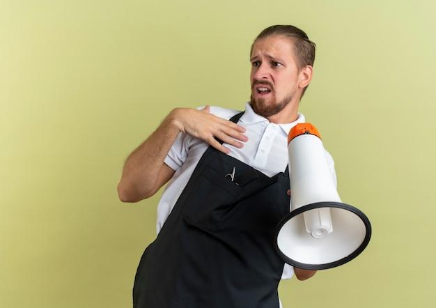 Niezadowolony młody przystojny fryzjer, trzymając głośnik i kładąc rękę na piersi, patrząc z boku na białym tle na oliwkowym tle z miejsca na kopię
