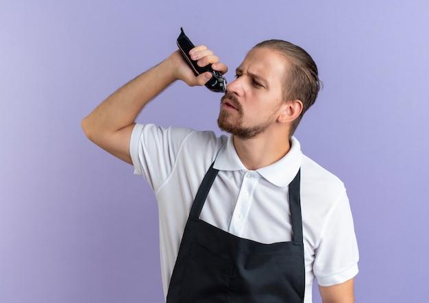 Niezadowolony młody przystojny fryzjer w mundurze trzymając maszynkę do strzyżenia włosów, przycinający własną brodę, patrząc z boku na białym tle na fioletowym tle