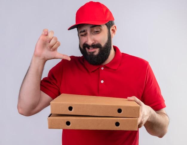 Niezadowolony młody przystojny kaukaski mężczyzna dostawy ubrany w czerwony mundur i czapkę, trzymając i patrząc na pudełka po pizzy i pokazując kciuk w dół na białym tle