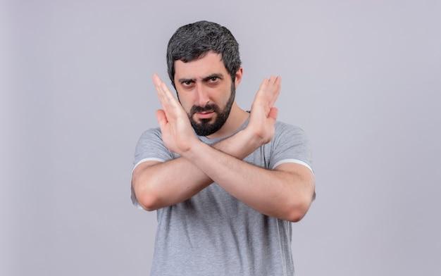Niezadowolony młody przystojny kaukaski mężczyzna gestykuluje nie na aparat na białym tle na białym tle z miejsca na kopię