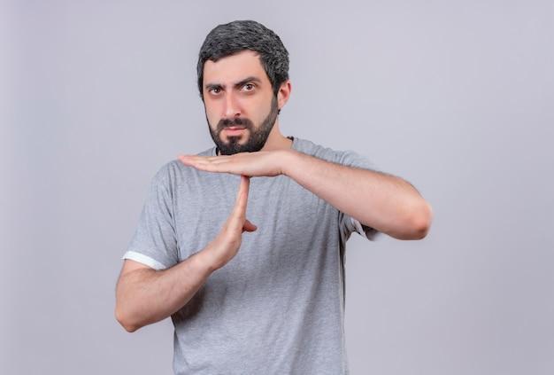 Niezadowolony młody przystojny kaukaski mężczyzna robi gest limitu czasu na białym tle