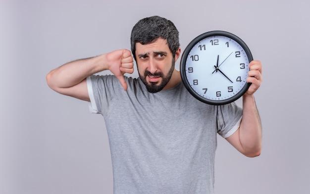 Niezadowolony młody przystojny kaukaski mężczyzna trzyma zegar skierowaną w dół i patrząc na bok na białym tle