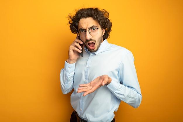 Niezadowolony młody przystojny kaukaski mężczyzna w okularach rozmawia przez telefon patrząc na kamery pokazując pustą dłoń na białym tle na pomarańczowym tle z miejsca na kopię