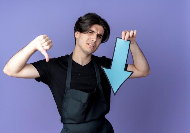 Niezadowolony młody przystojny mężczyzna fryzjer w mundurze trzymając papier w kierunku zaznacz kciuk w dół odizolowany na niebiesko