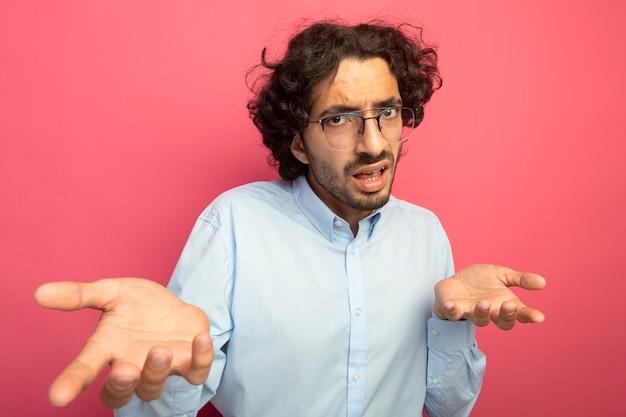 Niezadowolony młody przystojny mężczyzna w okularach patrząc z przodu pokazując puste dłonie na różowej ścianie
