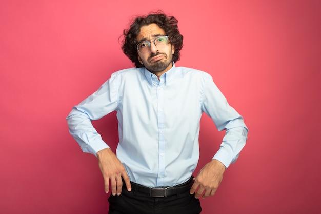 Niezadowolony młody przystojny mężczyzna w okularach, patrząc z przodu, trzymając ręce w powietrzu na białym tle na różowej ścianie