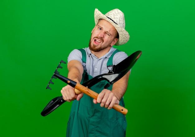 Niezadowolony młody przystojny ogrodnik słowiański w mundurze i kapeluszu, wyglądający na wyciągającego łopatę i grabie w kierunku