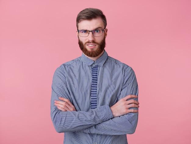 Niezadowolony młody przystojny rudy brodacz marszczy brwi, patrzy w kamerę z niesmakiem, ze skrzyżowanymi rękami stoi na różowym tle.