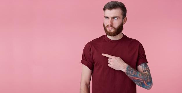Niezadowolony młody przystojny rudy brodaty mężczyzna w czerwonej koszuli, chce zwrócić twoją uwagę na skopiowanie miejsca po lewej stronie, wskazując palcami i pytająco patrzy na niego, stoi na różowym tle.