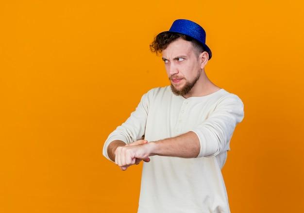 Niezadowolony młody przystojny słowiański facet w kapeluszu imprezowym, patrząc prosto, robisz jesteś spóźniony gest na białym tle na pomarańczowym tle z miejsca na kopię