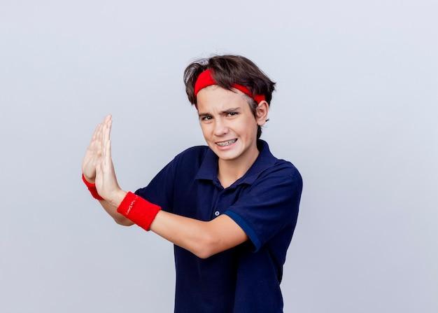 Niezadowolony młody przystojny sportowy chłopiec noszący opaskę i opaski na nadgarstek z aparatem ortodontycznym patrząc na aparat, nie wykonujący żadnego gestu z boku na białym tle na białym tle z przestrzenią do kopiowania