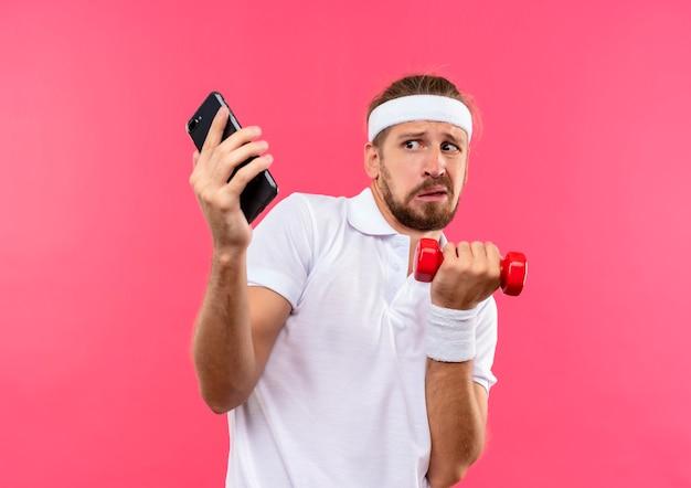 Niezadowolony młody przystojny sportowy mężczyzna w opasce i opaskach na rękę trzyma hantle i telefon komórkowy i patrzy na telefon odizolowany na różowej przestrzeni