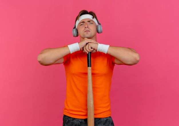 Niezadowolony młody przystojny sportowy mężczyzna w opasce, opaskach na rękę i słuchawkach, kładąc ręce na kij baseballowy na białym tle na różowym tle