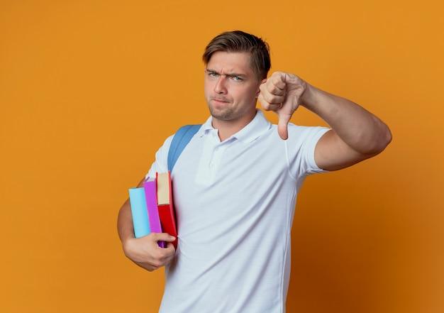 Niezadowolony młody przystojny student płci męskiej w plecaku trzymając książki