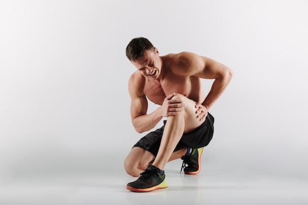 Niezadowolony młody sportowiec ma bolesne odczucia w nodze.