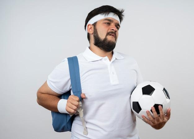 Niezadowolony młody sportowiec patrząc z boku na sobie opaskę i opaskę z plecakiem trzymając piłkę na białym tle na białej ścianie