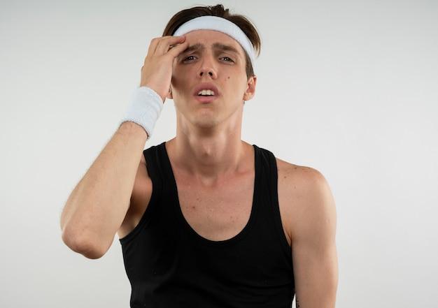 Niezadowolony młody sportowy facet ubrany w opaskę i opaskę, kładąc rękę na czole na białym tle