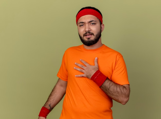 Niezadowolony młody sportowy mężczyzna w opasce i opasce kładzie rękę na piersi na białym tle na oliwkowym tle