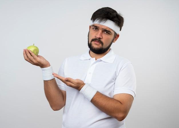 Niezadowolony młody sportowy mężczyzna w opasce i opasce trzyma i wskazuje ręką na jabłko na białej ścianie