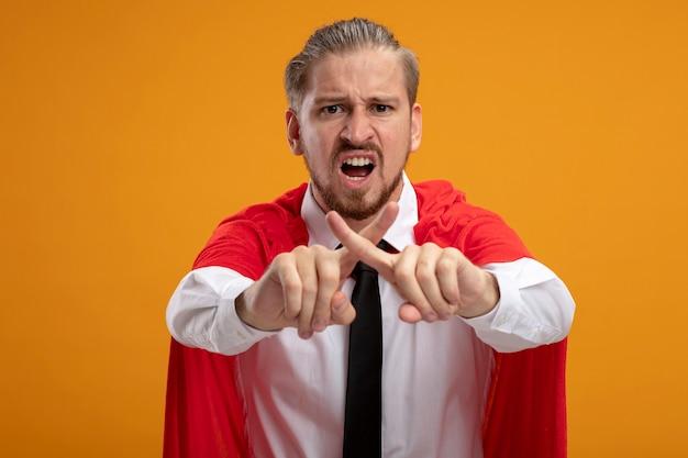 Niezadowolony młody superbohater facet w krawacie pokazujący gest nie na białym tle na pomarańczowym tle