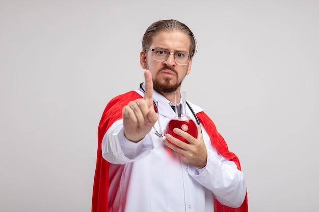 Niezadowolony młody superbohater w fartuchu medycznym ze stetoskopem i okularami