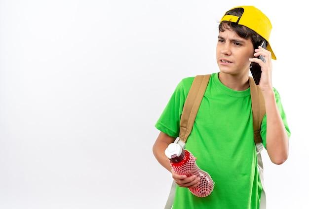 Niezadowolony młody szkolny chłopiec w plecaku z czapką trzymającą butelkę z wodą rozmawia przez telefon
