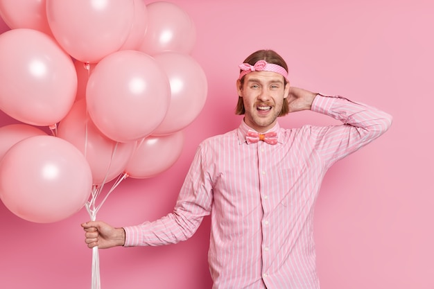 Niezadowolony, nieogolony europejczyk ubrany w świąteczne ubrania trzyma kilka nadmuchanych balonów z helem świętuje urodziny nadchodzi na imprezę odizolowaną na różowej ścianie