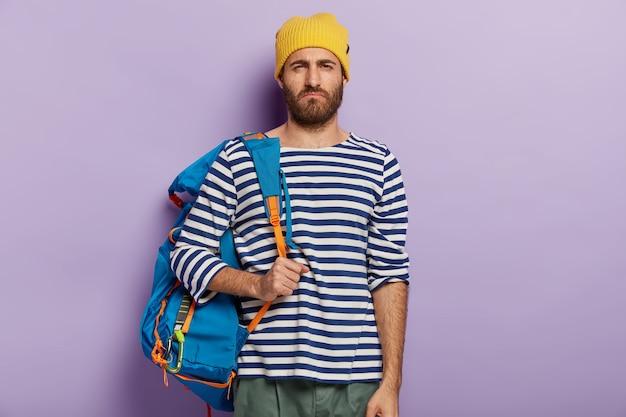 Niezadowolony, nieogolony mężczyzna uśmiecha się złośliwie, ma nieszczęśliwy wyraz twarzy, nosi turystyczny plecak