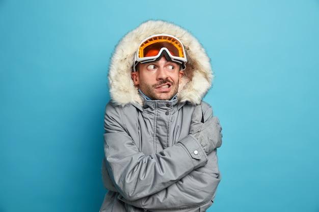 Niezadowolony, nieogolony młody człowiek trzęsie się i drży od zimna, nosi gogle narciarskie i obejmuje zimową kurtkę.