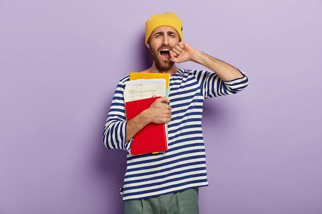 Niezadowolony, nieogolony młody człowiek ziewa ze zmęczenia, jest senny i wyczerpany, trzyma rękę przy otwartych ustach, trzyma kartki z notatnikiem i podręcznik