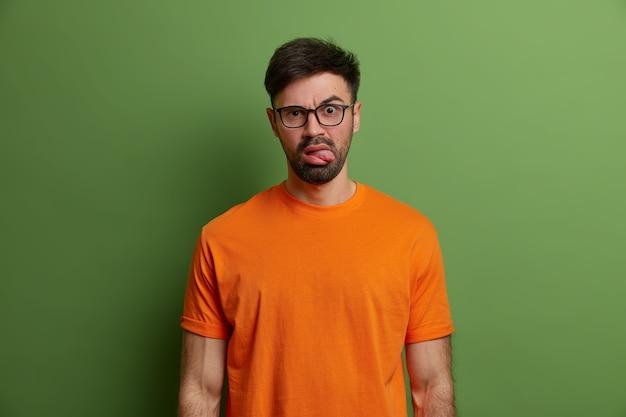 Niezadowolony, nieogolony młody europejczyk wystawia język, robi zaniepokojony niezadowolony wyraz twarzy, nosi przezroczyste okulary i jasnopomarańczową koszulkę, odizolowany na jasnozielonej ścianie