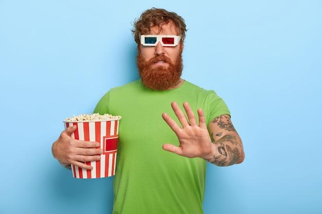 Niezadowolony nieszczęśliwy rudy facet w kinie odmawia rozmowy o filmie i postaciach po obejrzeniu