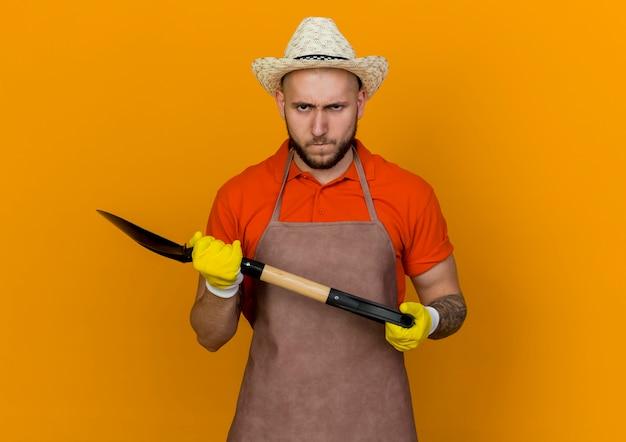 Niezadowolony ogrodnik w kapeluszu ogrodniczym i rękawiczkach trzyma łopatę