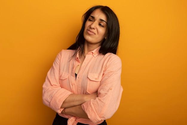 Niezadowolony patrząc na bok młoda piękna dziewczyna ubrana w różową koszulkę skrzyżowanie rąk na żółtej ścianie z miejsca na kopię