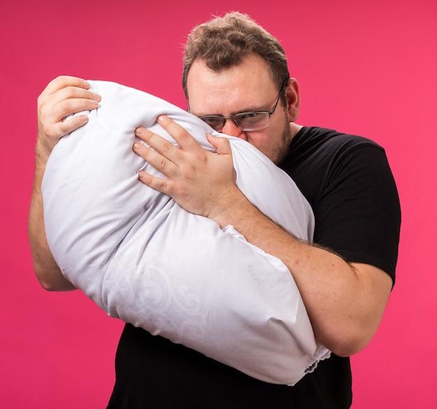 Niezadowolony, patrząc na kamerę, chory mężczyzna w średnim wieku przytulił poduszkę