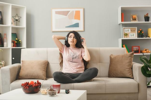 Niezadowolony, patrząc w górę, młoda dziewczyna w słuchawkach, siedząca na kanapie za stolikiem kawowym w salonie