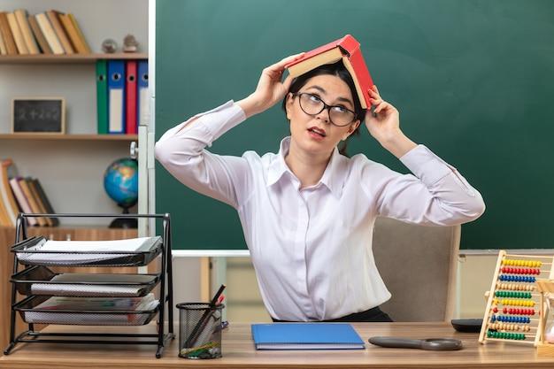 Niezadowolony, patrząc w górę, młoda nauczycielka w okularach, przykryta głową z książką, siedząca przy stole z szkolnymi narzędziami w klasie