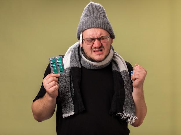 Niezadowolony, patrzący na aparat, chory mężczyzna w średnim wieku, ubrany w zimową czapkę i szalik trzymający pigułki
