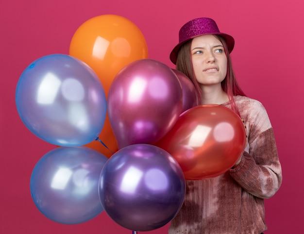 Niezadowolony, patrzący na bok młody piękny kapelusz na imprezę trzymający balony izolowane na różowej ścianie