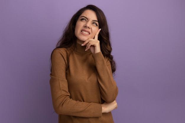 Niezadowolony, patrzący w górę, młoda piękna dziewczyna w brązowym swetrze z golfem, kładąca rękę na brodzie odizolowana na fioletowej ścianie