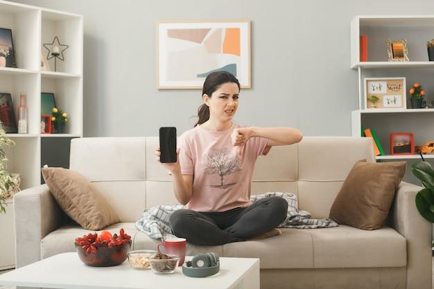 Niezadowolony pokazując kciuk w dół młoda dziewczyna trzyma telefon siedzący na kanapie za stolikiem kawowym w salonie