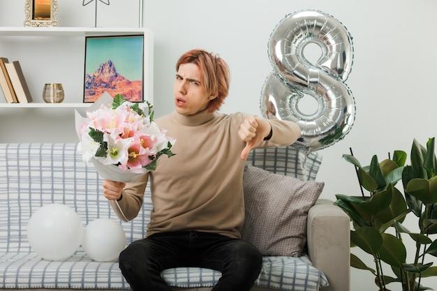 Niezadowolony pokazując kciuk w dół przystojnego faceta na szczęśliwy dzień kobiet trzymający bukiet siedzący na kanapie w salonie