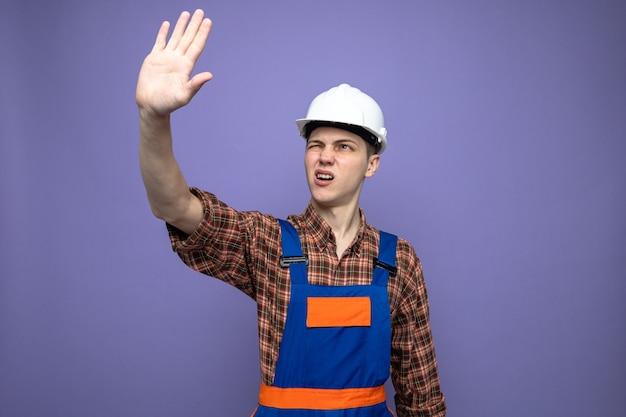 Niezadowolony pokazywanie gestu zatrzymania młodego męskiego budowniczego w mundurze