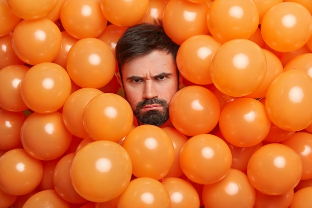 Niezadowolony ponury kaukaski mężczyzna z gęstą brodą wygląda nieszczęśliwie i marszczy brwi, twarz wystawia głowę z pomarańczowych balonów smutny, że sam spędza urodziny nie przyjmuje gratulacji zirytowany hałaśliwym przyjęciem