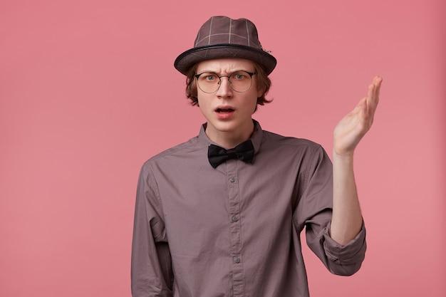 Niezadowolony, poważny młody, elegancko ubrany facet trzymający rękę w górze patrząc na aparat przez okulary moralizujący, broni swojego punktu widzenia, wygłasza wykład moralny, na różowym tle