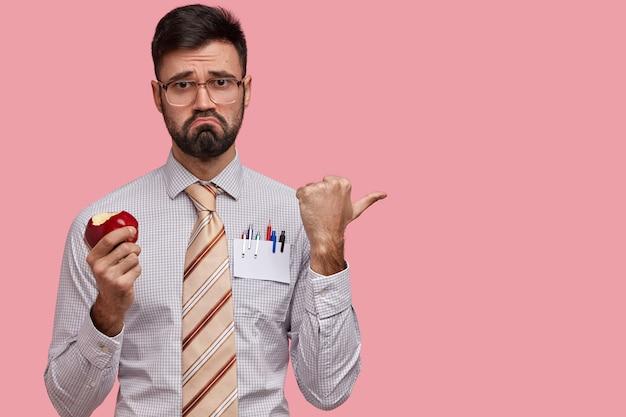 Niezadowolony pracownik biurowy zjada jabłko, marszczy brwi, wskazuje kciukiem w bok, ubrany w formalną koszulę i krawat